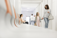 Mother and daughter holding hands walking in hospital corridor