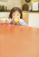 Girl drinking orange juice at breakfast table