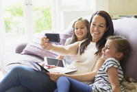 Mother and daughters taking selfie on living room sofa