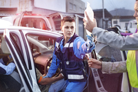 Rescue workers with IV bag tending to car accident victim