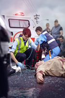 Rescue workers tending to car accident victim in road 11086024892| 写真素材・ストックフォト・画像・イラスト素材|アマナイメージズ