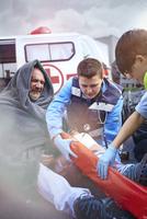 Rescue workers preparing vacuum leg splint on car accident victim in road 11086024899  写真素材・ストックフォト・画像・イラスト素材 アマナイメージズ