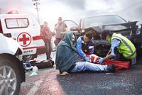 Rescue workers preparing vacuum leg splint on car accident victim in road