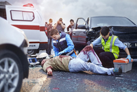 Rescue workers tending to bloody car accident victim in road