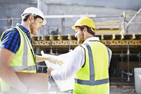 Construction worker and engineer reviewing blueprints at construction site