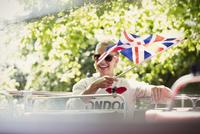 Smiling woman waving British flag on double-decker bus 11086025050  写真素材・ストックフォト・画像・イラスト素材 アマナイメージズ