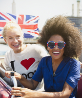 Portrait enthusiastic friends with British flag riding double-decker bus