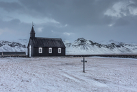 Church and graveyard in snowy remote mountain landscape, Budir, Snaefellsnes, Iceland