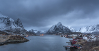 Snow covered mountain range above fishing village at dusk, Reine, Lofoten Islands, Norway
