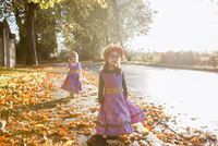 Toddler girls in Halloween costumes walking in autumn leaves