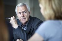 Senior businessman listening to businesswoman in meeting