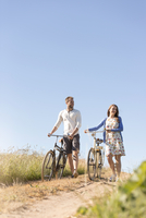 Young couple walking bicycles on dirt road below sunny blue sky