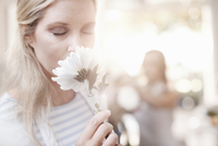 Woman smelling white gerber daisy