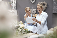 Smiling florists using digital tablet in flower shop