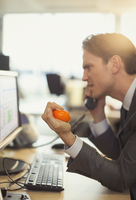 Angry businessman squeezing stress ball and talking on telephone at computer in office