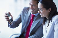 Businessman showing cell phone video to businesswoman
