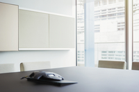 Conference phone on table in vacant conference room