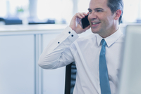 Smiling businessman talking on cell phone in office