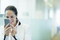 Smiling businesswoman using cell phone in office corridor