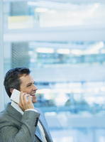 Smiling businessman talking on cell phone in office 11086026208| 写真素材・ストックフォト・画像・イラスト素材|アマナイメージズ