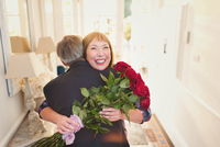 Happy women receiving rose bouquet and hugging husband