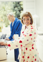 Portrait smiling mature woman drinking coffee in bathrobe at kitchen counter