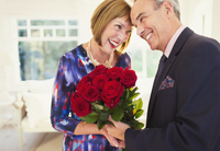 Affectionate well-dressed mature couple with rose bouquet