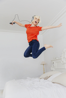 Playful woman jumping on bed listening to music with headphones and mp3 player