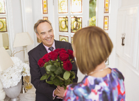 Mature man giving rose bouquet to wife