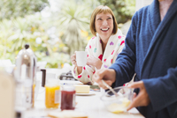 Smiling mature woman drinking coffee in bathrobe at breakfast