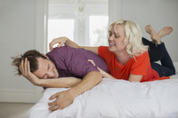 Playful wife tickling husband on bed