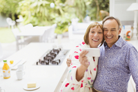 Smiling mature couple taking selfie in kitchen