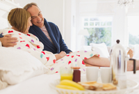 Affectionate mature couple in bathrobes enjoying breakfast in bed