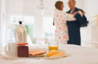 Mature couple in bathrobes dancing behind breakfast in bed