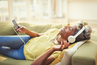 Comfortable mature woman listening to music with headphones and mp3 player on living room sofa