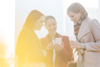 Smiling businesswomen texting and drinking coffee outdoors