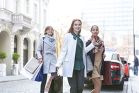 Smiling women with shopping bags crossing city street