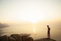 Runner on rocks looking at sunset ocean view 11086026441| 写真素材・ストックフォト・画像・イラスト素材|アマナイメージズ