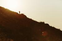 Silhouette of runner ascending hillside at sunset 11086026443| 写真素材・ストックフォト・画像・イラスト素材|アマナイメージズ