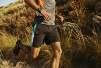 Man running on trail through tall grass