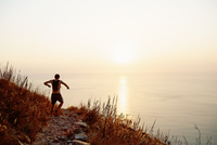 Male runner with backpack descending craggy trail overlooking sunset ocean 11086026464| 写真素材・ストックフォト・画像・イラスト素材|アマナイメージズ