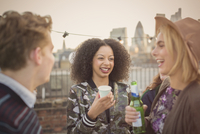 Young adult friends drinking and enjoying rooftop party