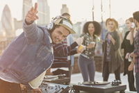 Portrait enthusiastic DJ gesturing at rooftop party