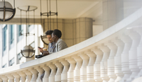 Corporate businessman and businesswoman with coffee and cell phone at railing