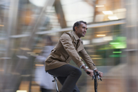Corporate businessman riding bicycle