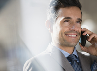 Close up smiling corporate businessman talking on cell phone