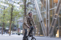 Corporate businessman riding bicycle outside modern building