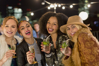 Portrait enthusiastic young women drinking cocktails at party