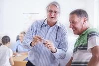 Doctor showing senior man digital thermometer at checkup