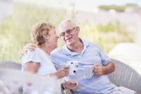 Senior couple hugging and drinking coffee on patio